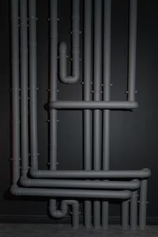 Sistema di tubi di drenaggio di plastica grigio complicato sulla parete