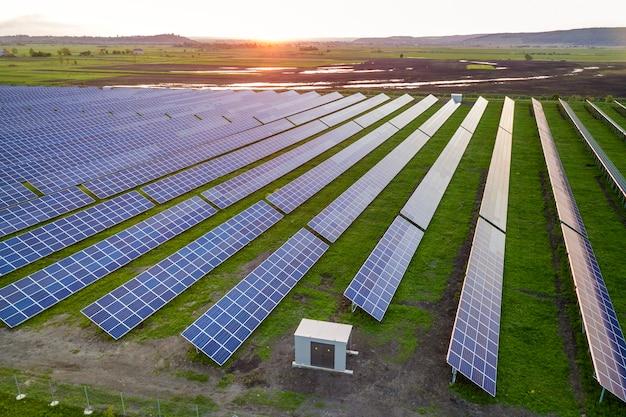 Sistema fotovoltaico blu solare dei pannelli fotovoltaici che produce energia pulita rinnovabile su paesaggio rurale e tramonto.