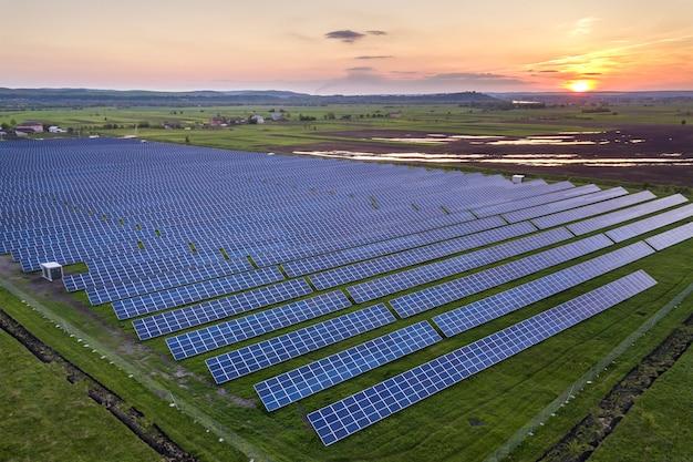 Sistema fotovoltaico blu solare dei pannelli fotovoltaici che produce energia rinnovabile pulita sul paesaggio rurale