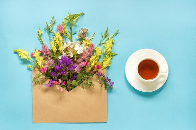 Sistemi i fiori variopinti in busta del mestiere e tazza di tè sul blu