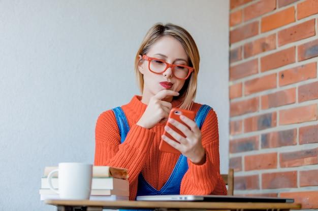 Sititng ragazza al tavolo con computer e cellulare