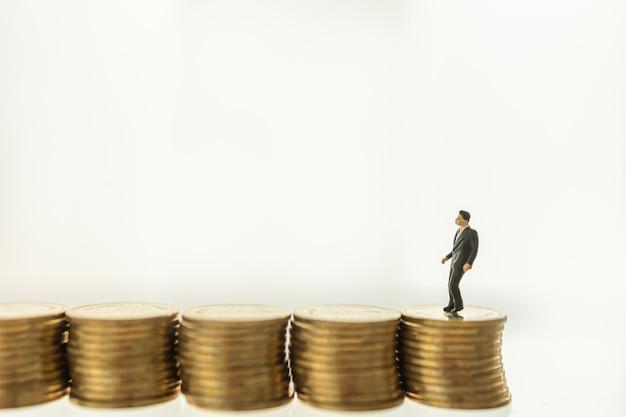 Situazione coronavirus (covid-19) business ed econony cocept. figura miniatura della gente dell'uomo d'affari con la maschera di protezione che sta e che cammina sulla pila di monete.