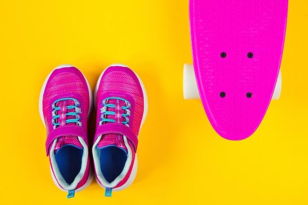 Skateboard rosa e scarpe da ginnastica su sfondo giallo piatto laici