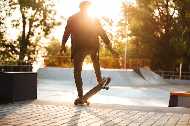 Skateboarder africano che pattina su una rampa concreta di skateboard