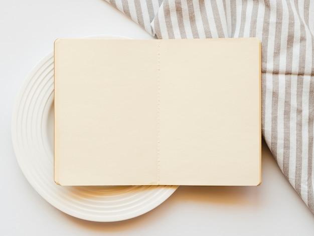 Sketchbook marrone pallido su un piatto bianco su uno sfondo bianco con una tovaglia grigia e bianca a strisce