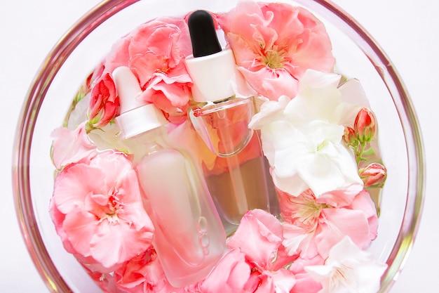 Skincare olio di siero con fiorellini in lastra di vetro. prodotto spa cosmetico per la bellezza del viso. trattamento concept pelle. contagoccia di olio essenziale, essenza di aromaterapia