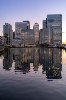Skylines che costruiscono a canary wharf nella penombra britannica di tramonto di londra