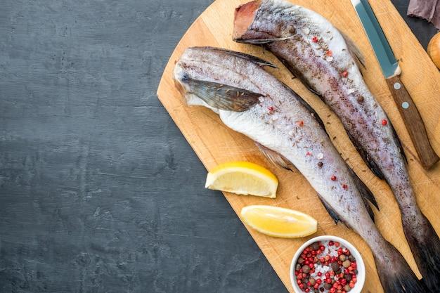 Slave pesce crudo sul tagliere di legno su sfondo scuro mix di limone e pepe