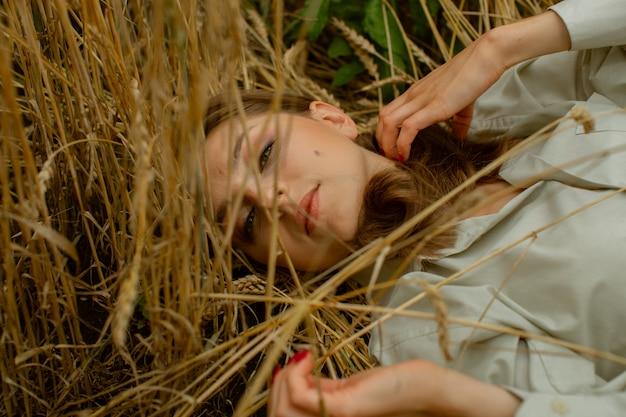 Slavyanka giace in un campo con spighe di grano maturate.