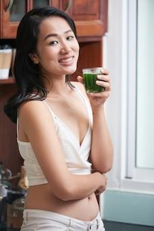 Slim donna etnica con un bicchiere di succo