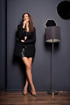 Slim lady in minigonna e giacca nera oversize in piedi vicino alla lampada da terra nella stanza