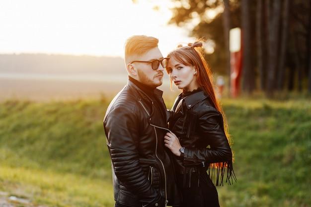 Slim ragazza alla moda con lunghi capelli rossi che abbraccia un ragazzo brutale con la barba e occhiali da sole indossando al tramonto