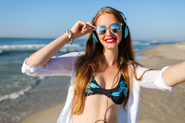 Slim ragazza dai capelli lunghi con pelle pallida che fa selfie mentre riposa in località balneare. ritratto all'aperto di signora felice in occhiali da sole ascoltando musica e godersi la brezza dell'oceano nel fine settimana.
