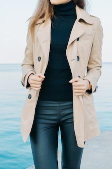 Slim ragazza elegante in un cappotto beige e pantaloni neri sullo sfondo del mare