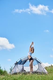 Slim ragazza felice scalatore in piedi vicino alla tenda sulla cima di una collina contro il cielo blu e nuvole, alzando le mani in aria, godendo la mattina d'estate in montagna