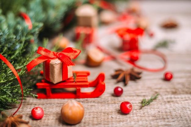 Slitta con regali di natale e decorazioni sul legno.