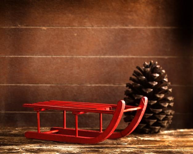 Slitta rossa in legno con pigna marrone