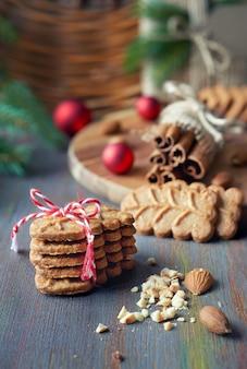 Sloseup su biscotti alle mandorle con bastoncini di cannella, trifogli, mandorle e ramoscelli dell'albero di natale