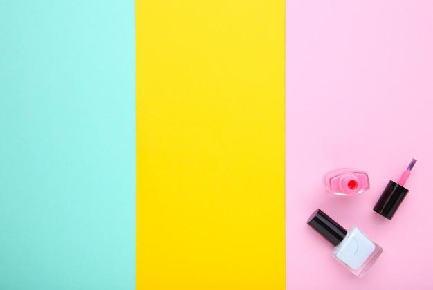 Smalti per unghie rosa e blu su sfondo colorato