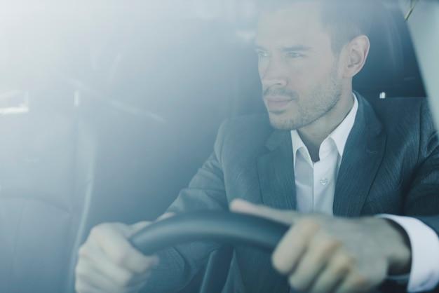Smart giovane uomo d'affari alla guida della macchina