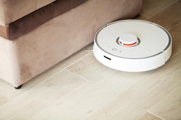 Smart house. il robot aspirapolvere funziona sul pavimento di legno in un salotto.