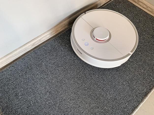 Smart house. il robot dell'aspirapolvere funziona sul pavimento in un salone.