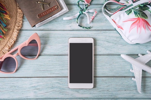 Smart phone a schermo vuoto con accessori da viaggio estivi e oggetti su fondo in legno