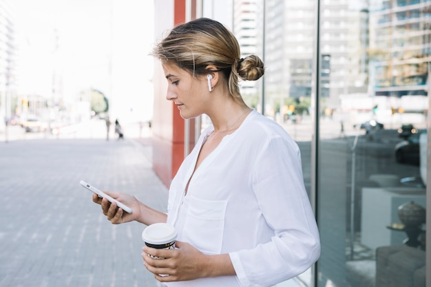 Smart phone biondo della tenuta della giovane donna e tazza di caffè asportabile in mani