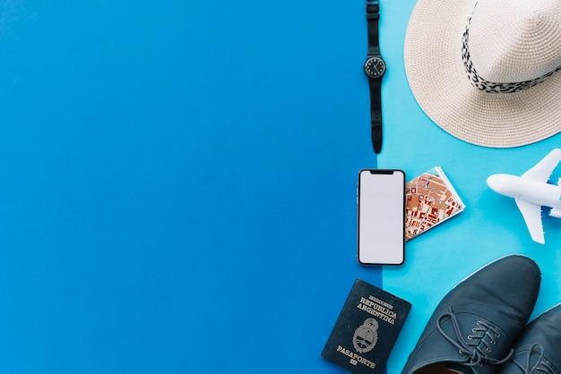 Smart phone; carta geografica; passaporto; aeroplanino giocattolo; scarpe; orologio da polso e cappello su sfondo doppio con spazio per la scrittura di testo