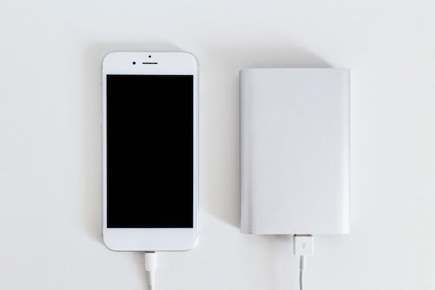Smart phone collegato con caricabatterie banca di potere su sfondo bianco