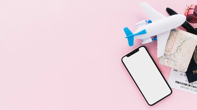 Smart phone con schermo vuoto con passaporto di viaggio; carta geografica; biglietti; aeroplano giocattolo e occhiali da sole su sfondo rosa