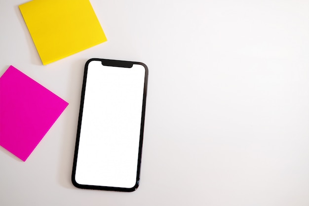 Smart phone con schermo vuoto vuoto bianco sul tavolo scrivania bianca.