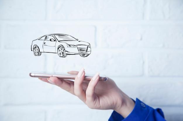 Smart phone della mano della donna con l'automobile in schermo