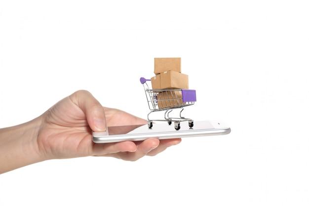 Smart phone della tenuta della mano della donna con le scatole di carta in un carrello.
