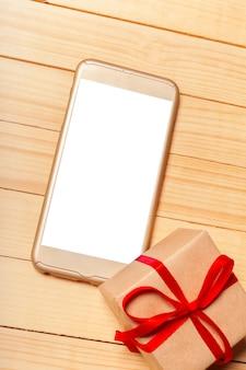 Smart phone e regalo su fondo di legno