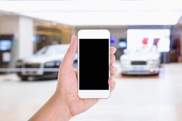 Smart phone mobile con lo schermo in bianco in un fondo vago della sala d'esposizione dell'automobile