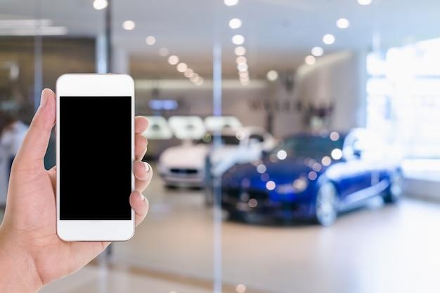 Smart phone mobile con lo schermo in bianco in una priorità bassa vaga della sala d'esposizione dell'automobile