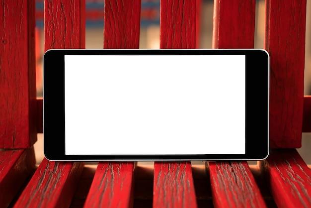 Smart phone mobile con lo schermo in bianco su legno rosso. tecnologia e concetto di stile di vita.