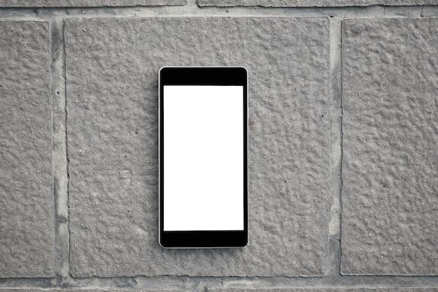 Smart phone mobile con lo schermo in bianco sul piatto di mattoni concreti. tecnologia e concetto di stile di vita.