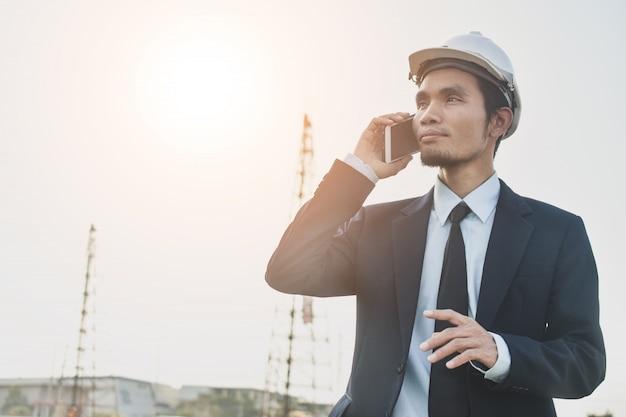 Smart phone mobile di conversazione dell'uomo d'affari al sito della costruzione di edifici