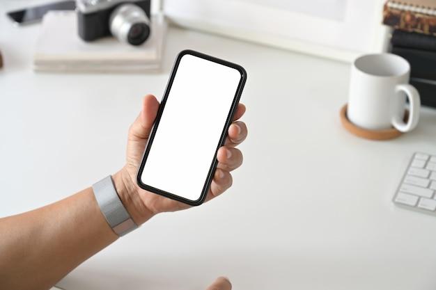 Smart phone mobile nella mano dell'uomo al lavoro di scrivania.