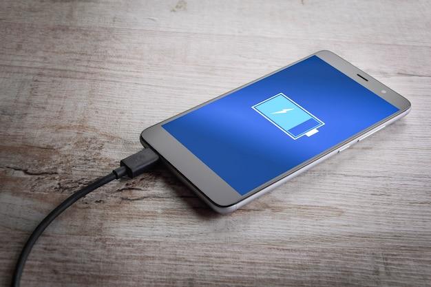 Smart phone mobili che fanno pagare sul fondo di bianco dello scrittorio di legno