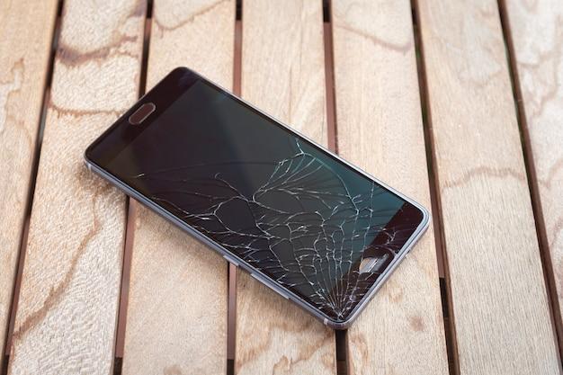Smart phone moderno mobile del touch screen con lo schermo rotto su fondo di legno. n