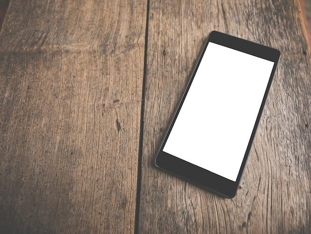 Smart phone nero con schermo vuoto nella tabella di legno