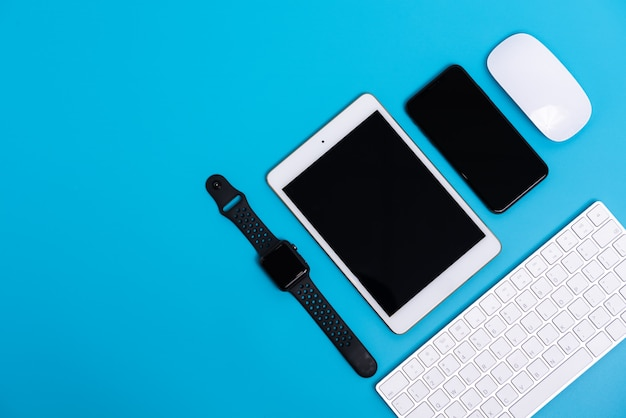 Smart phone, smart watch, tablet, mouse e tastiera su cielo blu, flat lay