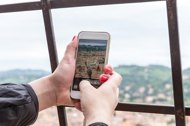 Smart phone turistico della tenuta della mano che prende immagine di bologna italia