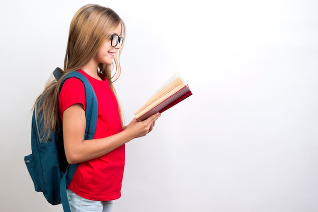 Smart schoolgirl reading bookbook