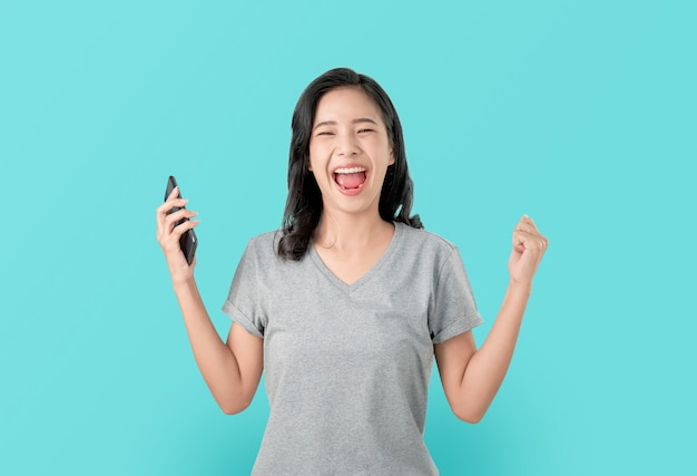 Smartphone asiatico della tenuta della donna con stupito per successo e guardare avanti sul blu.