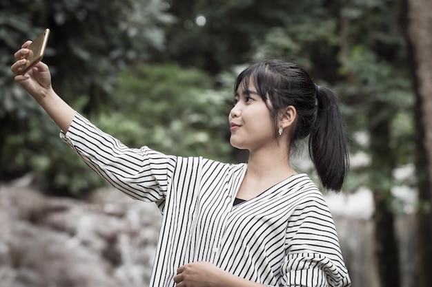 Smartphone asiatico della tenuta della giovane donna per i selfies alla foresta