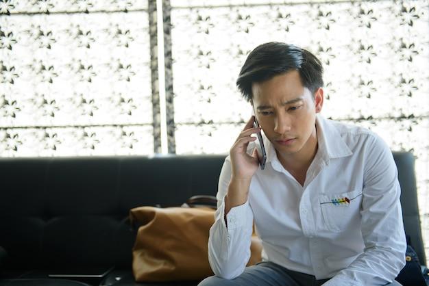 Smartphone asiatico di uso dell'uomo, giovane che chiama telefono cellulare